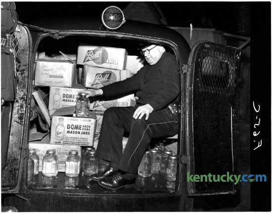Lexington officer James Kenton shows there was not much room for those arrested after the liquor was loaded in a police vehicle, Jan. 11, 1951. The house at 536 Brown Court was raided in what police described as the biggest moonshine raid in local history. 188 gallons of the liquor were well hidden under the kitchen floor, which was accesiable through a trap door. All of the moonshine was stored in fruit jars, officers said. Four men were arrested during the raid. Herald-Leader archive photo