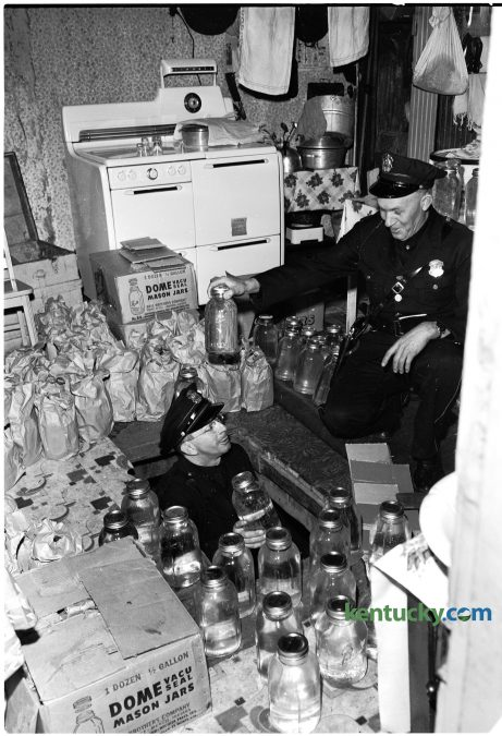 Lexington police officer Harrison Sallee passes confiscated moonshine jars to officer Jesse Wilburn Jan. 11, 1951. The house at 536 Brown Court was raided in what police described as the biggest moonshine raid in local history. 188 gallons of the liquor were well hidden under the kitchen floor, which was accesiable through a trap door. All of the moonshine was stored in fruit jars, officers said. Four men were arrested during the raid. Herald-Leader archive photo