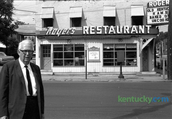 George Rogers in front of his restaurant at 601 West Main Street in June of 1965 after announcing plans to move the popular eatery to 808 South Broadway. Rogers bought the a former confectionery, located at the corner of Jefferson St. and West Main, in 1923. Rogers Restaurant featured home-style cooking and included hams he cured himself from hogs raised on his Woodford County farm. He sold the restaurant in 1974 to Charles Ellinger, who bought it as a Valentine's gift to his wife, Jan. Ellinger's son, Chuck Ellinger eventually took over the restaurant. Lexington's oldest restaurant closed it's doors on July 17, 2004. Published in the Lexington Herald June 19, 1965. Herald-Leader Archive Photo