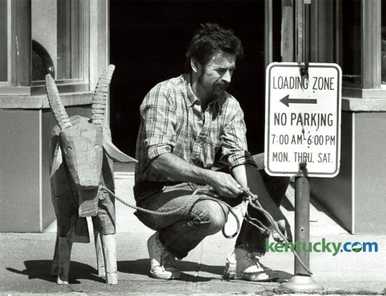 Adrian Swain tied a hand carved wooden goat to a no parking sign in front of his crafts shop in Morehead May 9, 1985. The goat, carved by Tom Sternal of Morehead, stood outside the shop to attract attention. Swain tied it up to discourage people from taking it. Photo by Ron Garrison | Staff