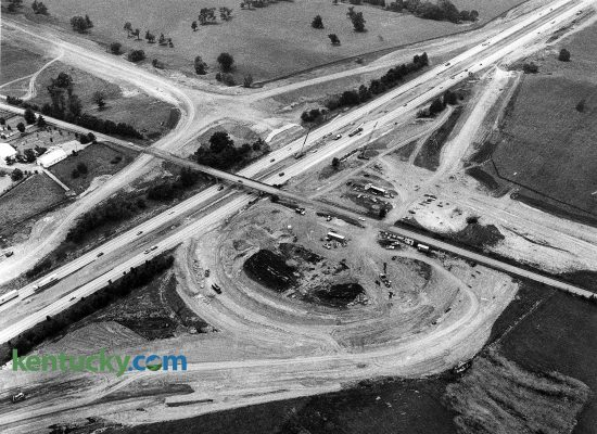 "Construction of the Man o' War Boulevard interchange with Interstate 75, June 17, 1988. I-75 runs towards the top right of the picture while what would be come Man o' War Boulevard comes into the frame from the upper left corner. Man o' War replaced Bryant Road, which shown here going over the interstate, was torn down in October 1988. Today a portion of Bryant Road exist to the west of I-75. Six months later, this last part of the Man o' War project was completed with little fanfare. Man o' War had been listed on city plans since the 1930s, but for many years, it was to be called Tiverton Way. The Urban County Council decided in 1974 that it would be named Man o' War Boulevard, after the famous race horse who never raced in Kentucky but retired to stud here. The road was completed and widened in segments over the years. The first section of road -- between Richmond Road and Palumbo Drive -- was opened in 1975. A second section opened four years later, a third four years after that. Man o' War was built by the state. It was planned, designed and will be maintained by Lexington. The state paid $37.6 million of the cost. The city paid $11 million. Along with the new I-75 interchange was a new sign on the interstate that said ""Man o' War,"" but the sign didn't indicate that the road went to Lexington. Man o' War as since been been further extended to the east, ending at Winchester Road.  Photo by Charles Bertram 