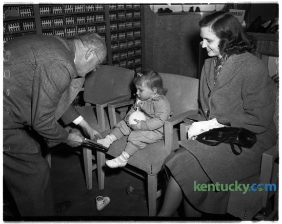"""Toddler Kathy Lewis being fitted by S.B. Foley with pair of shoes at Baynham Shoe Company, Feb. 4, 1949. The popular shoe store founded by three brothers at 135 East Main Street, operated for more then 50 years before closing in the 1970s. Their motto was """"shoes of distinction"""". Around the time of this photo, they were advertising white buck shoes for men for $4.95 a pair. The site of where the store was is where Phoenix Park is."""