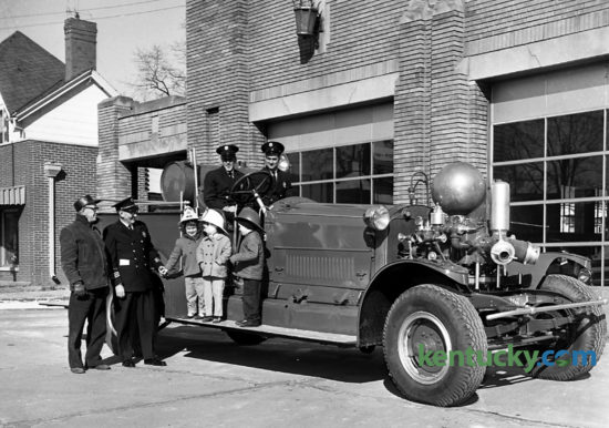 Old Engine No. 1 left Central Fire Station January 12, 1962 on its way to semi-retirement. The engine was given by the Fire Department to the Lexington Recreation Department to be used summers at the city playgrounds for children to climb on. Fireman Conrad Wells is in the driver's seat, and Fireman Raymond Stamper is beside him. Getting a free ride on the running board are Kime Tice Daniel, Debbie Watts and Stephen Wise. W.H. Brown, left, maintenance foreman of the recreation department, and Fire Chief HlL. Petit, watched the engine leave. The engine didn't run, but it was to be pulled from playground to playground during the summer and left at each  for four or five days. The engine was purchased in 1916 for $13,000 and made all major fire runs from then until 1949. Published in the Herald-Leader January 14, 1962. Herald-Leader Archive Photo