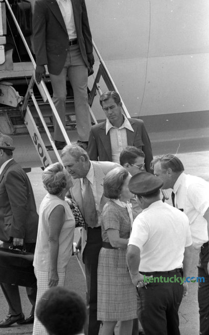 "Alabama Football Coach and Athletic Director Paul Bear Bryant greets Mrs. Charles Mitchell of Lexington after arriving at Blue Grass Field Sept. 21, 1973. The trip marked the first time Bryant, who coached at Kentucky for eight winning seasons, brought a team into Lexington to face the Wildcats. Bryant coached at UK from 1946-1953 before leaving for Texas A&M. He later went to Tuscaloosa was the legendary coach of Alabama for 25 years, leading the Crimson Tide to six national titles. Behind Bryant is Alabama basketball coach C.M. Newton, who came to Alabama after coaching at Lexington's Transylvania College for 12 seasons. After leaving Lexington in 1953, Bryant had a good relationship with Kentucky basketball coach Adolph Rupp and in 1969 he took Rupp's advice in hiring Newton to revive Alabama's basketball program. Newton went on to lead the Tide to three straight SEC titles. After a 30 year coaching career, he came back to Lexington in 1989 to be the athletic director at his alma mater, UK, where he served for 11 years. As for the game the following day, a Commonwealth Stadium record crowd of 54,100 chanted ""Beat Alabama"" and ""Let's skin the Bear"" to welcome back their former coach. Despite taking a 14-0 lead at the half, UK lost to heavily-favored Alabama, 28-14. Photo by E. Martin Jessee 