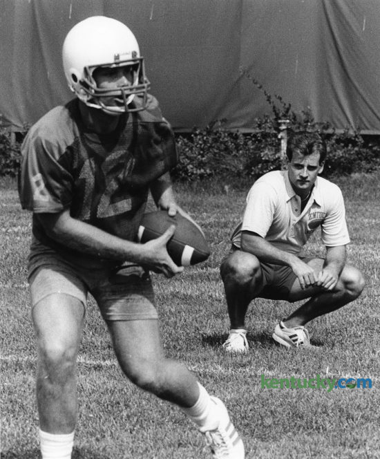 A knee injury forced Doug Martin, right, to give up his senior season of eligibility as a Kentucky quarterback in 1984. Instead, he launched his coaching career by working as a student assistant, here looking on in preseason camp Aug. 13, 1984 as then-freshman QB Bill Allen practiced. Now the head coach at New Mexico State, Martin will lead the Aggies against UK Saturday. Photo by Christy Porter | Staff