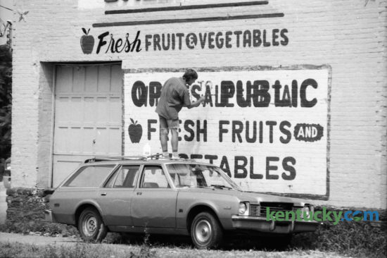 Dennis Myers, owner of Equus Art & Sign Painting, painted  over the word 'wholesale' to change it to Open to the Public, on the side of Baltrip's Fruits and Vegetables, 317 Bolivar Street on September 12, 1991. Photo by Charles Bertram | Staff