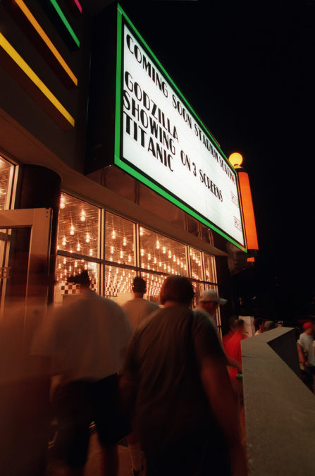 "People leaving the Woodhill Movie Theater after seeing the 7:00 p.m. show of the movie Godzilla, May 19, 1998. As the marque says, the film was shown on three screens. It was the ninth top grossing film released in the nation that year. ""Titanic"", the other movie on the marque, opened six months earlier in December 1997 and was so popular that it was still being shown in theaters. Photo by Joseph Rey Au"