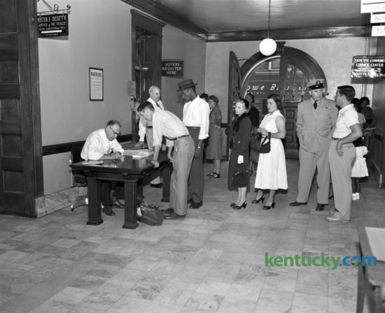 Because of the great number of Fayette countians registering to vote in the November election, the county clerk's office placed an extra desk in the hall outside the registration office on September 5, 1952 to take care of the overflow. At left, Robert Ledford, deputy clerk, registered Bill DeRossitt while others waited in line in the Fayette County Courthouse hallway. The voter registration office was to close on September 6 until after the election, which took place November 4. A total of 578 persons registered on the 5th. Of these, 339 were Democrats, 200 Republicans, and 39 Independents. That year's presidential election was between Republican, General Dwight D. Eisenhower, and Democrat Adlai Stevenson. Eisenhower was a landslide winner, carrying 39 states to Stevenson's 9, including Kentucky. Herald-Leader Archive Photo