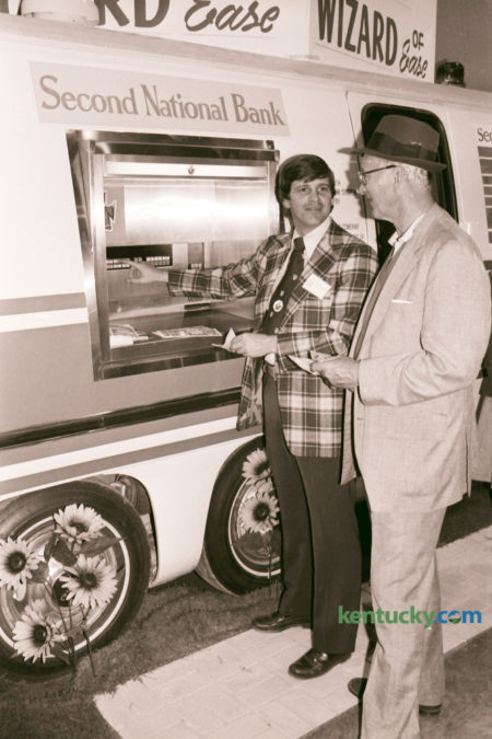 The first event held at the new Lexington Center in October 1976 was the Central Kentucky Expo, which featured industries and businesses of the area and included tours of the center and Rupp Arena. The Expo, held October 8-10 included the introduction of the automatic teller machine by Second National Bank. John Holmes, left, with the bank demonstrated the new machine to Gene Bryant. The bank announced that the automatic teller machines would be operating at the Woodpile and Fayette Mall branches by November 1. Photo by David Perry | Staff