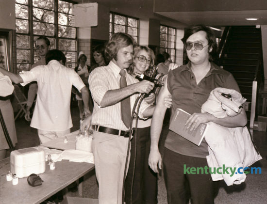 Donald Gross, right, a visiting assistant professor of political science at the University of Kentucky, stared straight ahead as he got his swine-flu shot October 28, 1976 at Memorial Coliseum from Paul Merkel, a state health department worker. Volunteer Judy Irvin, center, kept his sleeve up. This was the first of five local clinics for swine-flu shots for the general public. An estimated 5,000 people came to coliseum the first night and the health department expected to inoculate about 125,000 people before the program ended. Photo by David Perry | Staff