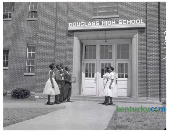 "Top honor seniors got together after the annual Award Day program at Douglass High School to admire the $200 name plaque their graduating class presented to the school at Class Night exercises on Monday May 26, 1958. Honor members of the senior class which ""did something"" about the fact that Douglass had never had a name marker over its front doors, include, from left, Charlesanna Brown, Delta Sigma Theta sorority $100 scholarship; Randolph Stewart, salutatorian, Female Education Society $100 scholarship and Alpha Phi Alpha fraternity award; Lonny Demaree, third-honor student; James Barlow Jr., valedictorian, Watkins English Plaque; June Taylor, leader award, and Carolyn Dawson, Female Education Society $100 scholarship. The name plaque was installed with neon lighting. Herald-Leader Archive Photo"