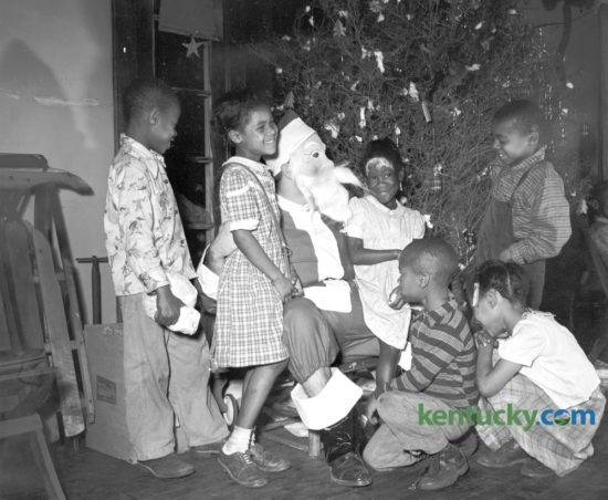 A pre-Christmas visit from Santa Claus highlighted the party given by the Lafayette Y-Teens December 20, 1948 for children at the Colored Orphans Home on Georgetown Street. Shown are, left to right, kneeling, Bobbie Lewis and Gordon Smith; Standing, William Cook, Betty McDowell, Henrietta Lewis and James Smith. Published in the Lexington Herald December 22, 1948. Herald-Leader Archive Photo