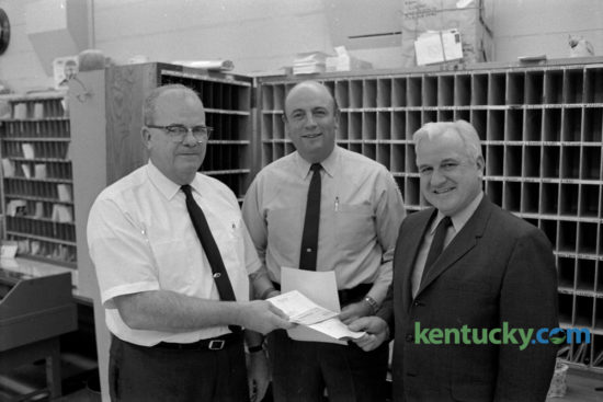 Postal employees Scott Johnson, left, clerk, and William B. Keightley,  center, carrier, received Superior Accomplishment Awards from Tom Bradley, right, superintendent of the Gardenside branch post office in December 1969. The award was for a contribution or performance that was over and above normal work requirements for an extended period of time. Keightley, the long time Kentucky basketball equipment manager who died March 31, 2008, would have turned 90 years old today. Herald-Leader Archive Photo