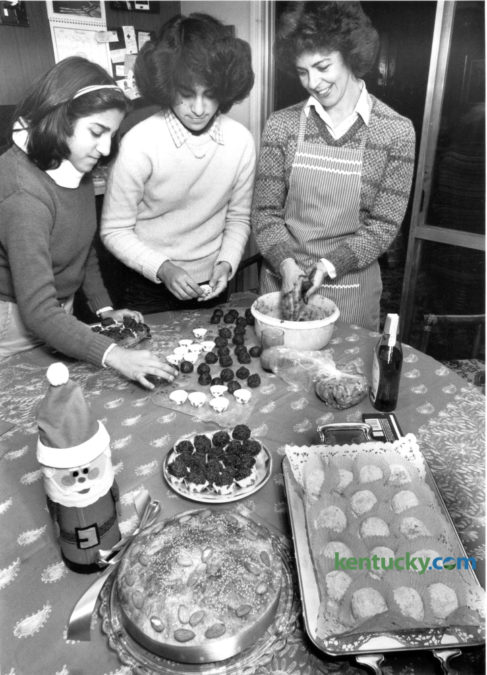 Helen Digenis, right, with her daughters Melina, 13, left and Emily, 15, prepared chocolate truffles and other holiday sweets in their kitchen on December 14, 1981. In the foreground are vassilopita, left, a Greek New Year's cake and kourambiethes, a Greek butter cookie, right. Photo by David Perry | Staff