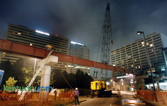 Workers erected one of the last beams supporting a walkway leading from the second floors of Victorian Square to the Lexington Center, July 17, 1993. Parts of Main and Vine streets were closed during the overnight hours as the 96-foot, 43,000-pound beam was put in position. The pedway opened later in the fall, giving pedestrians the ability to to walk through a complete circuit of enclosed passageways linking the Radisson Plaza Hotel, the Market Place, Victorian Square and the Lexington Center. Photo by Mark Cornelison | staff