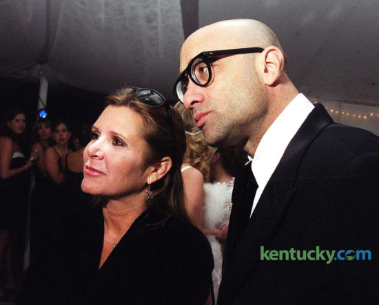 """Actress Carrie Fisher, with novelist Bruce Wagner, attending a Kentucky Derby party April 30, 1999 at the Kentucky Horse Park in Lexington. At the party, as a reporter was starting to ask her about the upcoming release of Star Wars: Episode I - The Phantom Menace, Fisher interjected: """"No, I have not seen it. I can always tell the face they make before they ask about it."""" Despite being forever linked to the Star Wars trilogy and the accompanying hype of the new film, Fisher said: """"I can't get sick of it. That would be a bad choice to make."""" Fisher, who died Dec. 27, 2016 was attending her first Derby the following day in Louisville. Photo by Jahi Chikwendui 