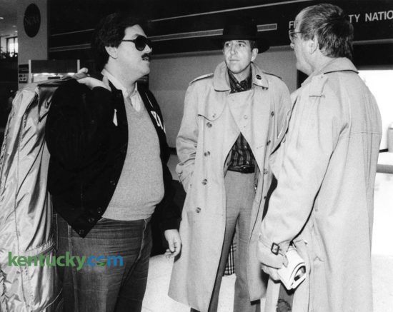 "Sportscaster Brent Musburger, center, waits for his luggage March 27, 1985 after arriving at Lexington's Blue Grass Airport for the NCAA Final Four at Rupp Arena. The lead voice for CBS Sports was greeted by NCAA hospitality volunteers as soon as he stepped off the plane, thrusting a tray of brightly wrapped candies towards him. ""Welcome to God's country. Have a bourbon ball,"" Pat Shropshire, the head of the airport hospitality committee urged in her best welcome-to-Lexington voice. No sooner had Musburger sidestepped the sweets than an eager army of volunteers surrounded him, dispensing NCAA buttons, patches and directions. He was among the first large group of tournament visitors to arrive in Lexington. Other passengers on Musburger's flight got the same treatment, and many appeared bewildered by the hearty hellos. Five days later, Musburger did play-by-play while Billy Backer provided color commentary on Villanova's historic NCAA championship upset over heavily-favored Georgetown. Photo by Christy Porter 