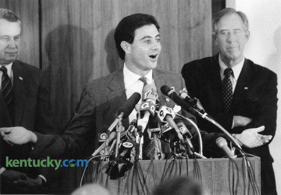 "Rick Pitino during his introductory news conference as the University of Kentucky basketball coach, June 1, 1989. Behind Pitino to the right is the man who hired him, first year athletic director C.M. Newton. The 36-year-old coach of the NBA's New York Knicks said he was up to the challenge of guiding Kentucky out of cloud of NCAA sanctions. ""Sanctions and probations just make it a little bit tougher,"" Pitino said in a Patterson Office Tower board room packed with reporters, 15 television cameras and UK officials. ""But we will overcome all obstacles in making Kentucky basketball rich again."" Kentucky faced a ban on post-season play for two years, a ban on live television appearances in 1989-90 and scholarship reductions resulting from an investigation that unveiled such NCAA rules violations as the sending of $1,000 to a recruit's father and cheating on a college entrance exam. Newton called Pitino's hiring the ""first step in rebuilding the basketball program."" In his remarks Pitino referred to a recent Sports Illustrated cover story, headlined ""Kentucky's Shame,"" that outlined the UK program he inherited. ""I promise to you people in this room today you'll see Kentucky on the cover of Sports Illustrated once again,"" Pitino said, ""and it will be cutting down certain nets. It won't be for what you saw last week."" Photo by David Sterling 