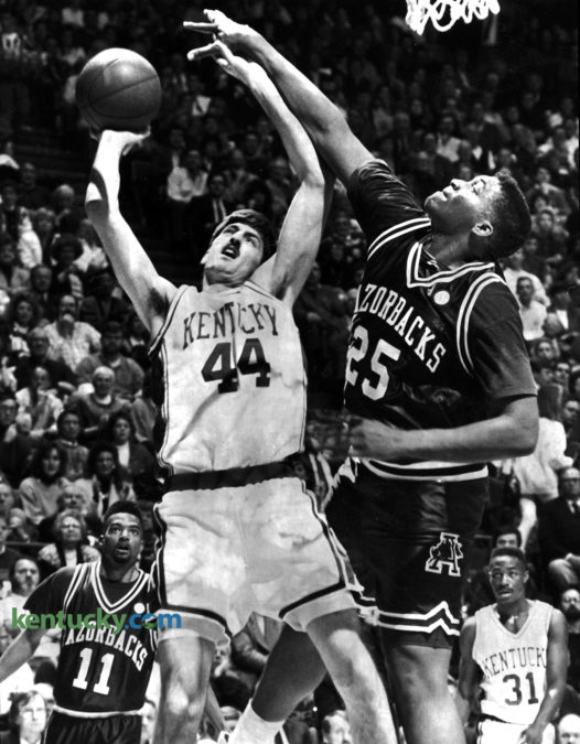 """University of Kentucky forward Gimel Martinez puts up a shot over Arkansas center Oliver Miller during the Razorbacks 105-88 win over the Cats, Jan. 25, 1992 at Rupp Arena. The long-awaited showdown between the two top-ten teams was the first meeting in league play since Arkansas joined the Southeastern conference. A record Rupp Arena crowd of 24,324 and what Arkansas Coach Nolan Richardson called """"the atmosphere of the Final Four"""" had no discernible impact on the senior-dominated Razorbacks, who held UK star Jamal Mashburn to a season-low four points, snapping a string of 19 double-figure games. Photo by Frank Anderson 