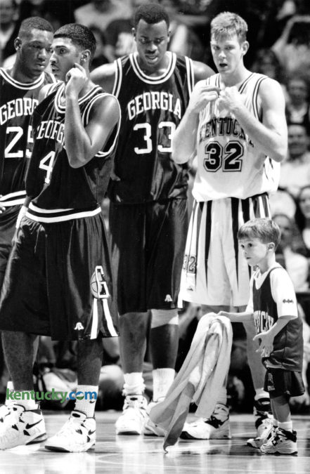 Ryan Pitino, Kentucky Coach Rick Pitino's 4-year-old son, was put to work during the UK-Georgia basketball game January 14, 1995, helping keep the Rupp Arena floor dry for the perspiring likes of Carlos Strong (25), Ty Wilson (4), Charles Claxton (33) and Jared Prickett (32). Photo by Frank Anderson | staff