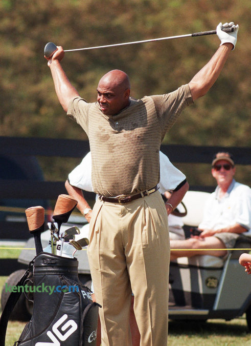 """Professional basketball star Charles Barkley stretches during the Central Baptist Hospital Charity Classic Aug. 22, 1998 at Lexington's Kearney Hill Golf Links. The Houston Rockets star sprayed comments like shots on his way to a 30-over 102. Barkley cussed a time or two and flung his """"Biggest Big Bertha"""" into the pond on No. 17 but always remained affable. On the first fairway, Jason Dunaway of Corinth asked Barkley to pose for a picture with 4-month-old Austin Rogers. """"I'm not supposed to,"""" Barkley said. Then, relenting, """"Let's do it right quick."""" After teeing off on No. 2: """"It was fat like Oprah."""" At No. 3, he stopped at a refreshment stand, bought a Diet Pepsi and tipped server Johna East. A fan asked if Barkley was wearing a lucky shirt. """"This is a free shirt,"""" he said. """"I guess you could consider that lucky."""" After shooting a quadruple-bogey 9 on No. 7: """"Ooh, I'm tired! That was a lot of work, y'all."""" When he hit his tee shot into the water and sent Big Bertha following on No. 17, 10-year-old Chad Fyffe of Frankfort waded in nearly chest high to retrieve the club. Barkley autographed the driver at the next tee. """"I have two drivers in my bag for special occasions,"""" Barkley said later. """"But I did hit that great drive on 18. I'm just mad I didn't hit that ball into the water sooner with that other driver."""" Photo by David Perry 