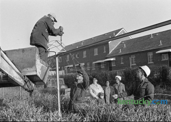 An eight-foot fence that separated blacks and whites since 1939 in the Blue Grass-Aspendale Housing Project comes down January 30, 1974. Taking down the barbed wire are, left to right, Jay Martin, Warren Gerton and Earl Osten, supervisor. Looking on are, left to right, residents, Mrs. Ruby Anderson and her son Steve; Mrs. Edith Hines, president of the Residents Council and Mrs. Lola Jones, also a council member. Photo by John C. Wyatt | Staff