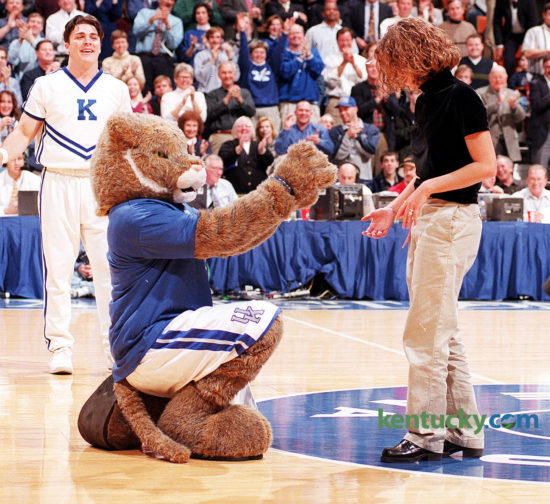 """A cheerleader led Sodan onto the court, where Duerson knelt and gave Sodan a ring. Then he carried her away as the crowd cheered. Sodan's reaction? """"Oh my gosh. Oh my gosh. Oh my gosh."""" That was a """"yes."""" Duerson, 21, and Sodan, 20, both UK students from Berea, had been dating off and on since middle school. They are still married today. Photo by Mark Cornelison 